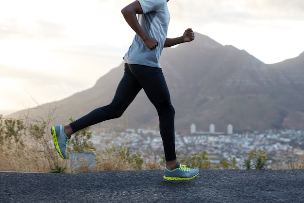 Uomo sano dalla pelle scura in azione, corre lungo la strada vicino alle montagne, indossa scarpe da ginnastica comode, abiti casual, ha un corpo sportivo. atleta maschio veloce pone contro il cielo. competizione di corse