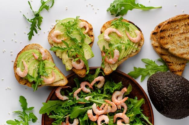 Здоровая вкусная еда. тосты с авокадо, креветками и салатом из рукколы. вид сверху, плоская планировка.