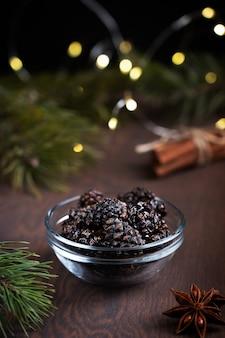 소나무 콘의 건강한 디저트는 계피와 함께 어두운 나무 테이블에 그릇에 크리스마스를 위해 제공