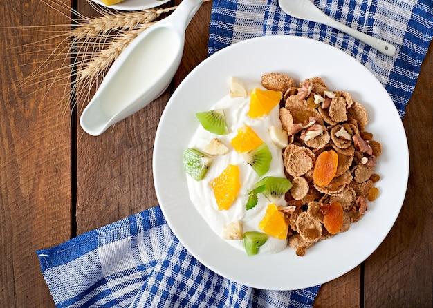 Здоровый десерт с мюсли и фруктами в белой тарелке на столе
