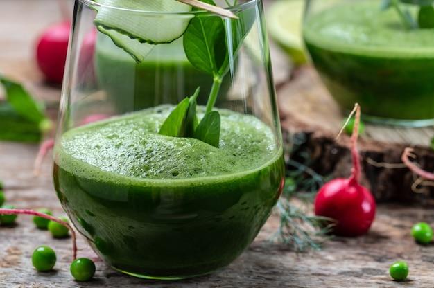 健康的なデトックスドリンク。ケールグリーンの新鮮なエンドウ豆、キュウリ、ほうれん草、ライムの緑の葉を使ったヘルシーなスムージー。
