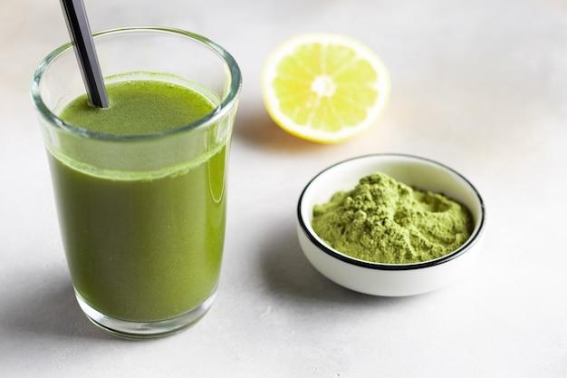 緑のスーパーフードパウダーで健康的なデトックスドリンク。植物ベースのカフェインドリンク