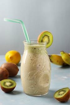 健康的なデトックススムージーキウイ、バナナ、新鮮な食材を使用した水色の表面のガラス瓶にレモン、ダイエットと減量の制御の概念、垂直形式