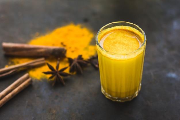 Латте с куркумой, полезный для детоксикации. золотое молоко с куркумой, специями и лимоном на темном фоне. полезный аюрведический напиток. укрепление иммунной системы. антиоксидант и суперпродукт