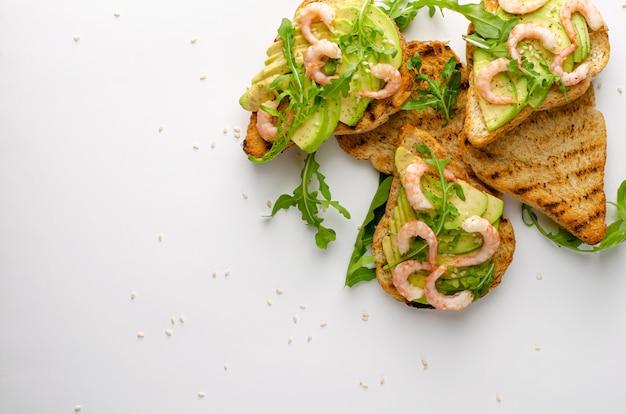 Здоровая диета закуска. авокадо тосты с рукколой и креветками на белой тарелке. верхний выстрел,