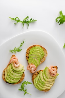 Healthy diet appetizer concept. avocado toasts with arugula and shrimps on white plate. overhead shot, vertical.
