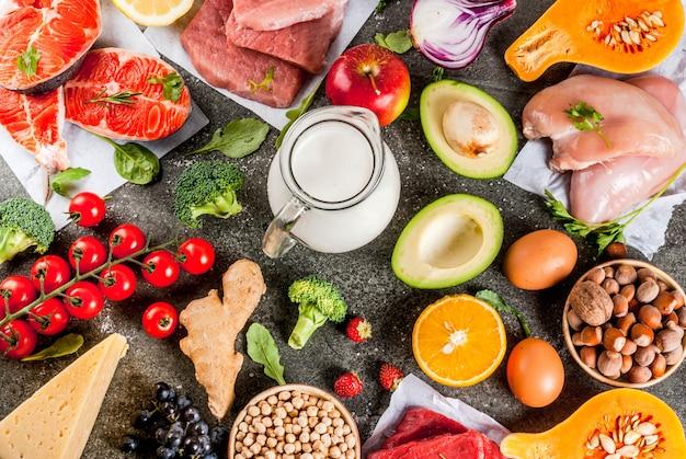健康的な食事の背景。有機食材、スーパーフード:牛肉と豚肉、鶏肉の切り身、サケ、魚、豆、ナッツ、牛乳、卵、果物、野菜。黒い石のテーブル、copyspaceトップビュー