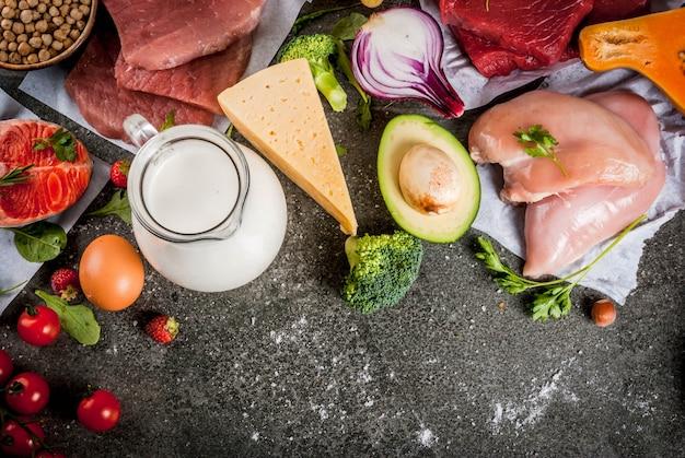 健康的な食事の背景オーガニック食品成分のスーパーフード:牛肉と豚肉の鶏肉のフィレサーモン魚豆ナッツミルク卵卵果物野菜黒い石のテーブル