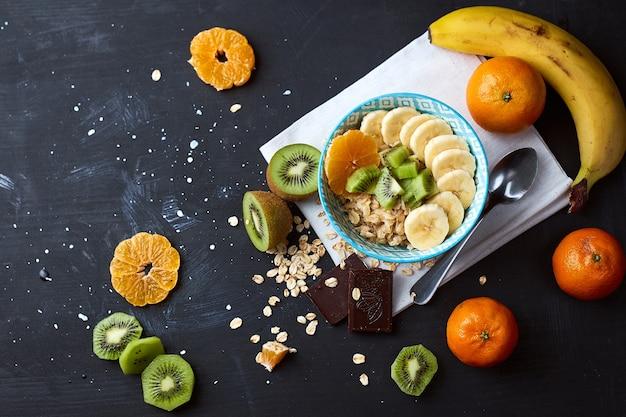 健康的な食事の朝食の概念。バナナ、キウイ、ダークチョコレート、柑橘類のオーツ麦のお粥。