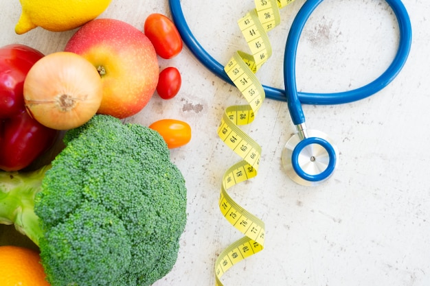 健康的な食事の概念、白い木製のテーブルに聴診器で生の新鮮な野菜