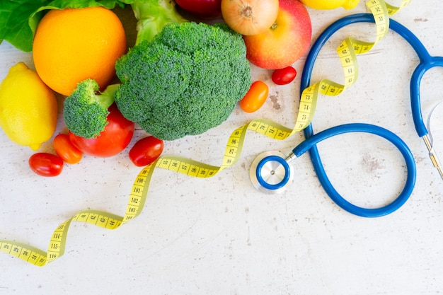 Healthy diet concept, raw vagetables with measuring tape and stethoscope on white table