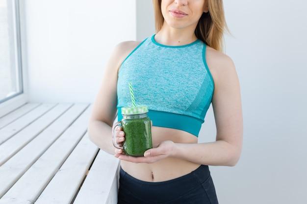 건강, 다이어트, 해독 및 체중 감량 개념 - 녹색 스무디 클로즈업이 있는 운동복을 입은 젊은 여성