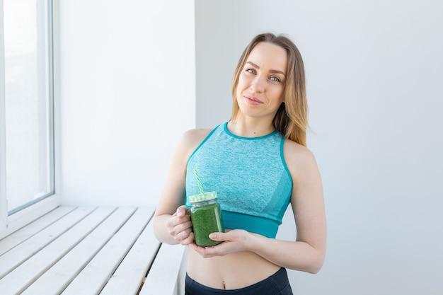健康、ダイエット、デトックス、減量の概念-グリーンスムージーとスポーツウェアの若い女性