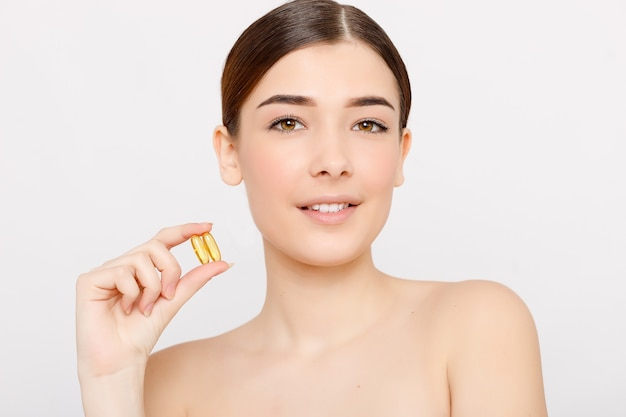 Здоровое диетическое питание. красивая улыбающаяся молодая женщина, держащая в руке таблетку рыбьего жира. крупный план. прием капсулы. витаминные и диетические добавки