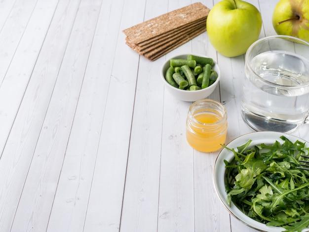 Healthy diet food on the table arugula green beans apple water honey cracker.
