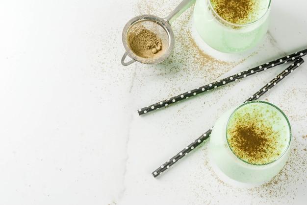 健康的なダイエット食品。ビーガンドリンク。朝食、デトックス、抗酸化物質。抹茶入りココナッツミルクスムージー。ガラス、ストロー、白い大理石のテーブルの上。上面図