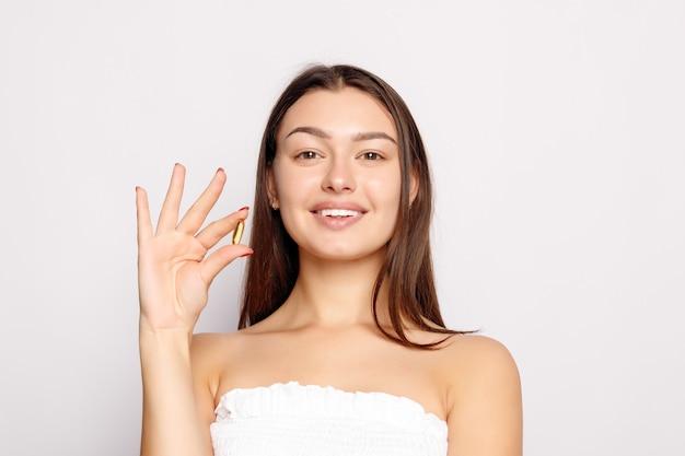 건강한 다이어트 영양. 생선 기름 알 약을 손에 들고 아름 다운 웃는 젊은 여자. 대구 간 기름, 오메가 3와 캡슐을 복용 하는 행복 한 여자의 근접 촬영. 비타민 및 건강 보조 식품. 높은 해상도