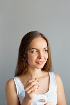 健康的な食事の栄養。ビタミン剤を服用している美しい笑顔の若い女性の肖像画