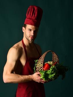 健康的な食事有機食品のコンセプト野菜を使った料理の準備野菜バスケットを持った男性シェフ