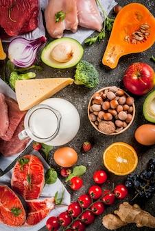 Healthy diet . organic food ingredients, superfoods: beef and pork meat, chicken filet, salmon fish, beans, nuts, milk, eggs, fruits, vegetables. black stone table,  copyspace top view