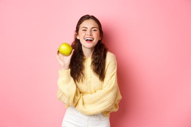 건강한 다이어트, 사람과 라이프 스타일 개념. 사과의 날은 의사를 멀리하고, 소녀는 맛있는 과일을 들고 분홍색 벽에 서서 카메라에 행복하게 웃고 있습니다.