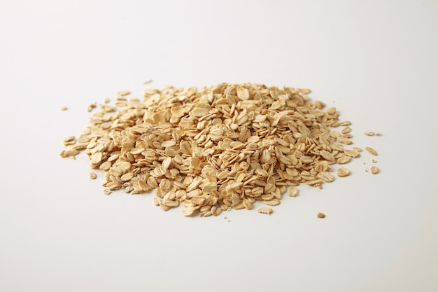 Healthy diet rolled oats isolated on white in center, prepared for cooking muesli for breakfast