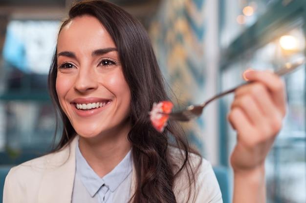 健康的なダイエット。笑顔とトマトをしながらフォークを使用して誠実で穏やかなかわいい女性