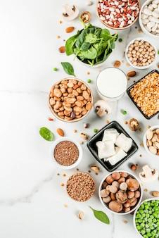 健康的な食事ビーガンフード、野菜たんぱく源:豆腐、ビーガンミルク、豆、レンズ豆、ナッツ、豆乳、ほうれん草、種子。白いテーブルのトップビュー。
