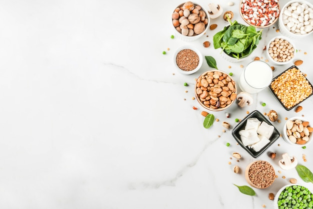 Healthy diet vegan food veggie protein sources tofu vegan milk beans lentils nuts soy milk spinach and seeds on white table