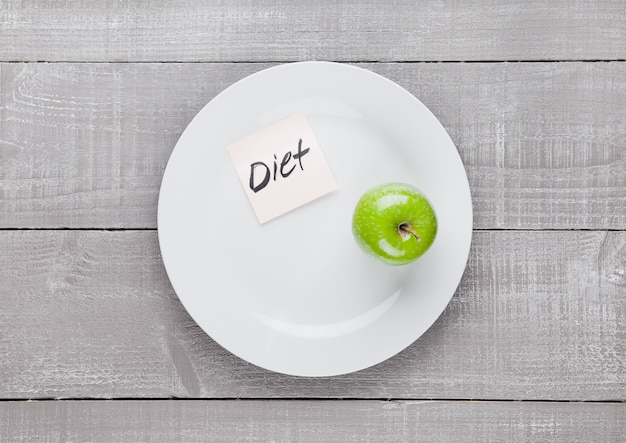 Healthy diet with fresh organic apple on the plate on wooden board