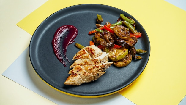 Healthy, dietary food - grilled chicken fillet with grilled vegatebles in a black ceramic plate on colored background. close up