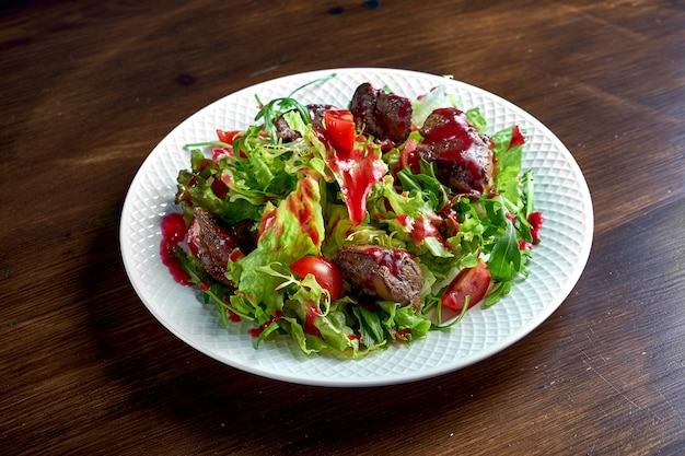Healthy and dietary salad mix with berry sauce, fried chicken liver and cherry tomatoes, served in a white plate on a wooden surface