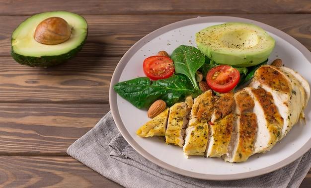Здоровый диетический салат с куриным филе, авокадо, орехами и свежими овощами. Premium Фотографии