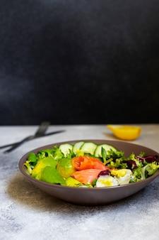 サーモン、アボカド、カボチャの種、新鮮な野菜、レモンのヘルシーダイエットサラダを灰色のテーブルで提供しています。健康的な食事のコンセプトです。黒の背景、テキスト用のスペース