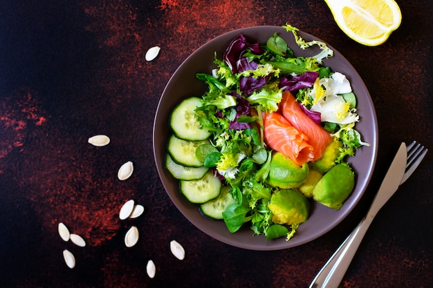 Healthy dietary salad with salmon, avocado, pumpkin seeds, fresh vegetables and lemon. the concept of healthy eating. dark background, top view, copy space