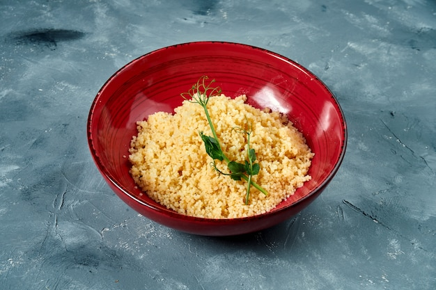 Healthy and dietary side dish - couscous porridge in a burgundy bowl on a concrete surface