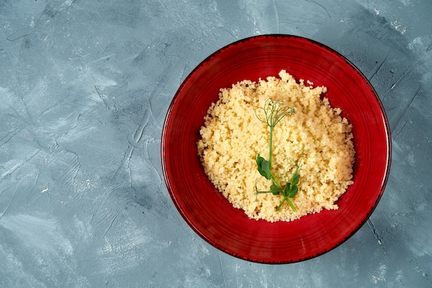 Healthy and dietary side dish - couscous porridge in a burgundy bowl on concrete. top view.
