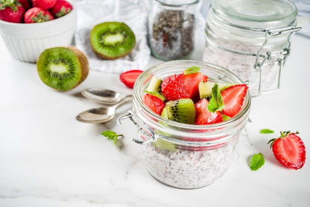 Healthy dietary vegan breakfast, yoghurt with chia seeds and fresh fruits, strawberries, kiwi.white marble background copy space