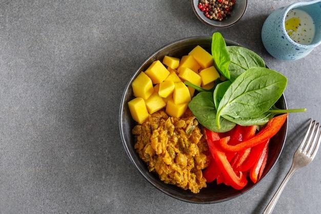 회색 배경에 접시에 야채와 망고를 곁들인 건강한 다이어트 부처 그릇. 확대