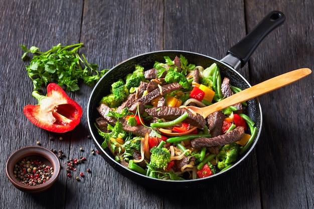 ヘルシーなディナー:ビーフファジタと野菜:ブロッコリー、インゲン、黄色と赤のピーマン、パセリ、タマネギをフライパンで、暗い木製のテーブルの上に木のスプーンで添えて、上面図、クローズアップ