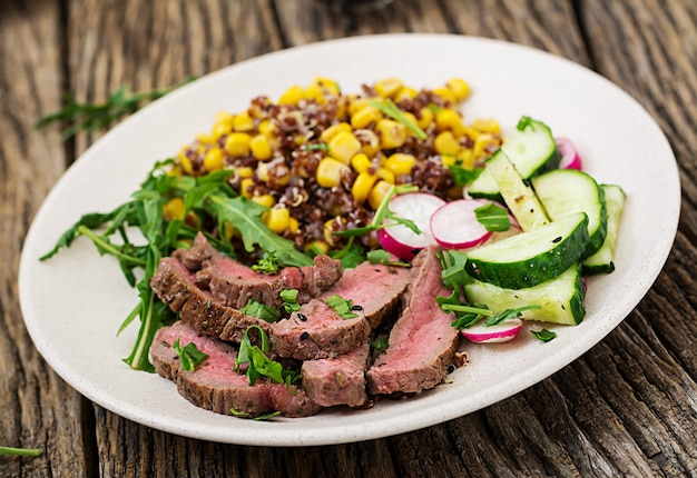 Healthy dinner. bowl lunch with grilled beef steak and quinoa, corn, cucumber, radish and arugula on wooden table. meat salad.