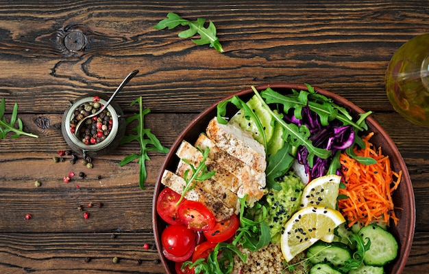 Healthy dinner. buddha bowl lunch with grilled chicken and quinoa, tomato, guacamole, carrot, red cabbage, cucumber and arugula on wooden table. flat lay. top view