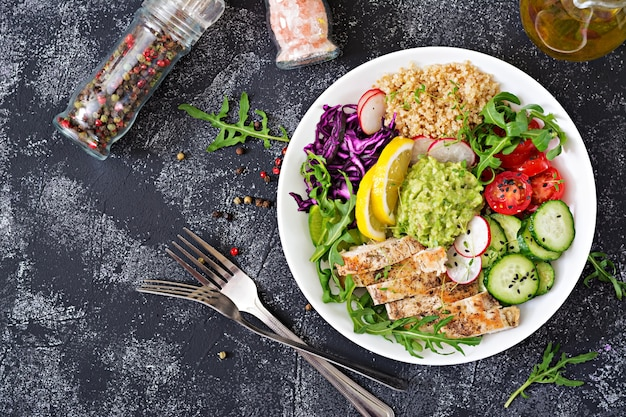 Healthy dinner. buddha bowl lunch with grilled chicken and quinoa, tomato, guacamole, red cabbage, cucumber and arugula. flat lay. top view