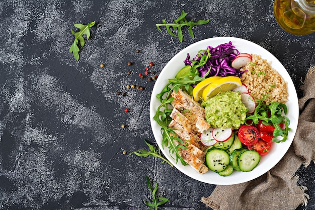 Healthy dinner. buddha bowl lunch with grilled chicken and quinoa, tomato, guacamole, red cabbage, cucumber and arugula on gray table. flat lay. top view