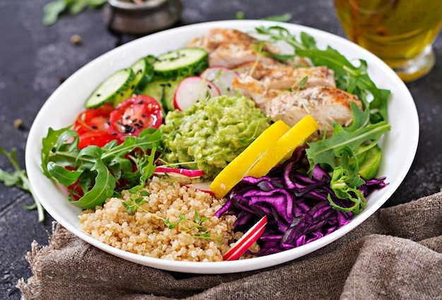 Healthy dinner. buddha bowl lunch with grilled chicken and quinoa, tomato, guacamole, red cabbage, cucumber and arugula.