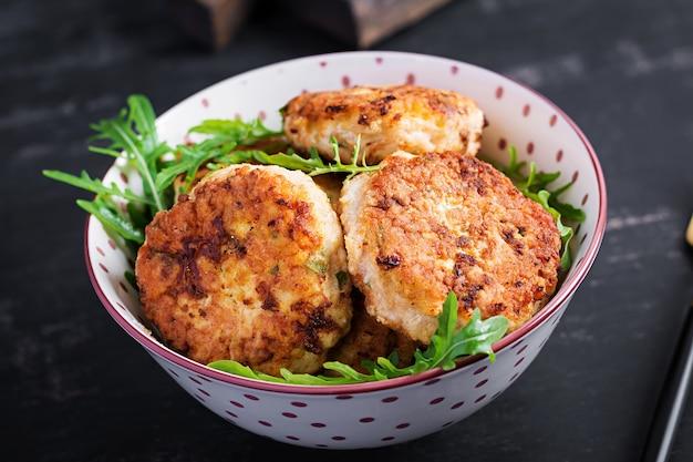Здоровый ужин. куриные котлеты в миске на темном фоне.