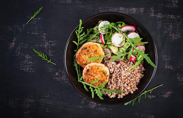 Здоровый ужин. обеденная миска с гречневой кашей, жареными куриными котлетами и салатом из свежих овощей из рукколы, огурца и редиса. вид сверху, плоская планировка