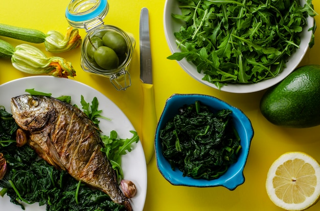 Healthy dinner or lunch with baked dorada fish or sea bream garnished with spinach and arugula on yellow background