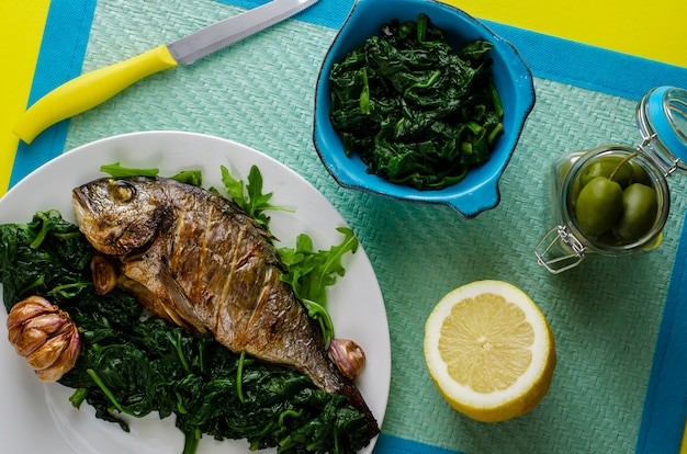 Healthy dinner or lunch with baked dorada fish or sea bream garnished with spinach in a bowl on blue background