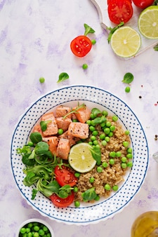Healthy dinner. slices of grilled salmon, quinoa, green peas, tomato, lime and lettuce leaves. flat lay. top view